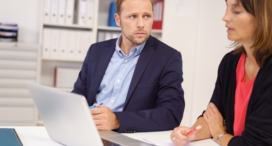 Worried businessman listening to a middle-aged female colleague as they sit together at a table in the office sharing a laptop computer